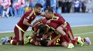 Venezuela players mob teammate Jose Rondon as they celebrate his goal against Colombia during their first round Copa America 2015 soccer match at Estadio El Teniente in Rancagua